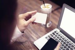 Nahaufnahme des Mannes übergibt das Halten der Visitenkarte und arbeitet an Laptop im Café mit dem Internet und trinkt Latte lizenzfreies stockbild