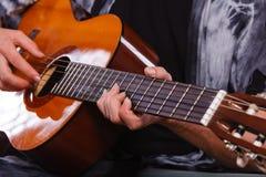 Nahaufnahme des Mannes Akustikgitarre spielend Lizenzfreie Stockfotografie