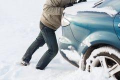 Nahaufnahme des Mannes das Auto drückend fest im Schnee Lizenzfreies Stockbild