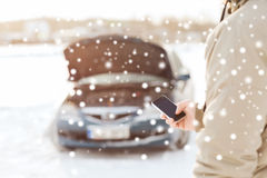 Nahaufnahme des Mannes mit defektem Auto und Smartphone Stockbilder