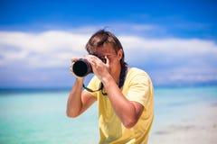 Nahaufnahme des Mannes mit einer Kamera auf weißem Sandstrand Stockfotografie