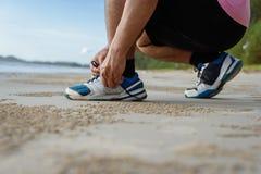 Nahaufnahme des Mannes Schnürsenkel auf dem Strand binden lizenzfreie stockbilder