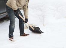 Nahaufnahme des Mannes Schnee von der Fahrstraße schaufelnd Stockfotos