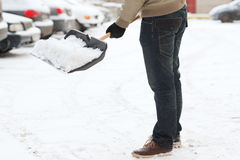 Nahaufnahme des Mannes Schnee von der Fahrstraße schaufelnd Stockfoto