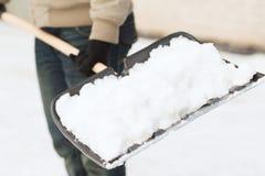 Nahaufnahme des Mannes Schnee von der Fahrstraße schaufelnd Lizenzfreie Stockbilder