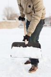 Nahaufnahme des Mannes Schnee von der Fahrstraße schaufelnd Stockfotografie