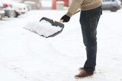Nahaufnahme des Mannes Schnee von der Fahrstraße schaufelnd Stockbilder