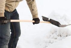 Nahaufnahme des Mannes Schnee von der Fahrstraße schaufelnd Stockbild