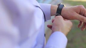 Nahaufnahme des Mannes setzt eine Uhr auf seine Hand draußen stock video