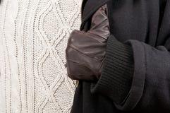 Nahaufnahme des Mannhandschuhs, der schwarzen Jacke und der gestrickten Strickjacke Lizenzfreie Stockfotos
