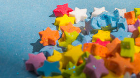 Nahaufnahme des mehrfarbigen Sternes formt auf blaues Papier Lizenzfreies Stockbild