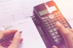 Nahaufnahme des menschlichen Buchhalters Berechnungen beim Sitzen machend am Schreibtisch im Büro Stockbild