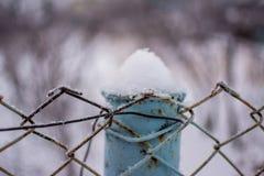 Nahaufnahme des Metallzauns bedeckt mit gefrorenem Schnee Lizenzfreie Stockfotos