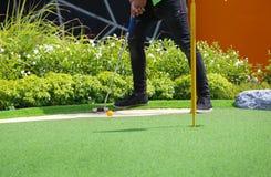 Nahaufnahme des Minigolflochs mit Schläger und Ball Stockfotografie