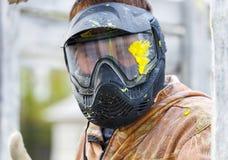 Nahaufnahme des männlichen Gesichtes in der Paintballmaske mit großem Spritzen Stockfotografie