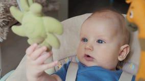 Nahaufnahme des Monat-alten Spiels des Babys 6 im elektrischen Schwingen zu Hause stock video footage