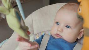 Nahaufnahme des Monat-alten Spiels des Babys 6 im elektrischen Schwingen zu Hause stock video