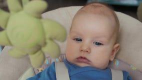 Nahaufnahme des Monat-alten Spiels des Babys 6 im elektrischen Schwingen zu Hause stock footage