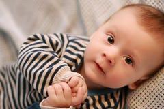 Nahaufnahme des netten Babys tragend in der gestreiften Strickjacke Stockbild