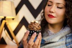 Nahaufnahme des netten Mädchenholdingkleinen kuchens des gelockten Haares stockbild