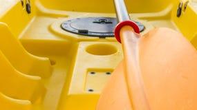 Nahaufnahme des orange Paddels und des undeutlichen gelben Kajaks Lizenzfreie Stockbilder
