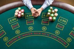 Nahaufnahme des Pokerspielers mit Chips am grünen Kasinotisch stockbild
