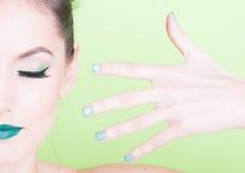 Nahaufnahme des professionellen grünen Makes-up mit zusammenpassenden Nägeln Lizenzfreies Stockfoto