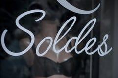 Nahaufnahme des Rabattzeichens 'SOLDES 'auf Französisch auf Fenster lizenzfreie stockbilder