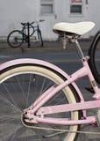 Nahaufnahme des Rades und Seat eines Rosas gestalteten das Fahrrad, das auf Straße geparkt wurde und zugeschlossen war Ein blaues Stockfotos