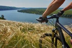 Nahaufnahme des Radfahrers, der Fahrrad auf der Wiese in der Landschaft gegen schöne Landschaft hält Lizenzfreie Stockfotos
