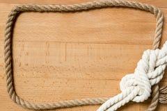 Nahaufnahme des Rahmens gemacht vom Seil und vom Marineknoten über hölzernem Schreibtisch Stockbilder