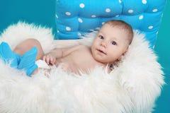Nahaufnahme des reizenden Babys stillstehend auf Pelzbett über blauem backgr Lizenzfreie Stockfotos