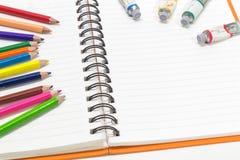 Nahaufnahme des rosa orange Anmerkungsbuches und der farbigen Bleistifte, Wasserfarbe Lizenzfreie Stockfotografie