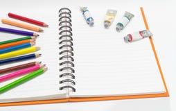 Nahaufnahme des rosa orange Anmerkungsbuches und der farbigen Bleistifte, Wasserfarbe Stockfotos
