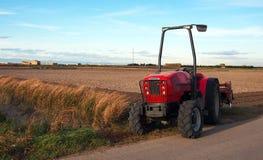 Nahaufnahme des roten Traktors der Landwirtschaft, der Feld über blauem Himmel kultiviert Lizenzfreies Stockbild
