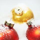 Nahaufnahme des Rotes u. der Goldweihnachtskugeln im Schnee Lizenzfreies Stockfoto