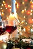 Nahaufnahme des Rotweins in den Gläsern, in der Kerze und im Flitter Lizenzfreie Stockfotografie