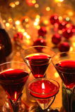 Nahaufnahme des Rotweins in den Gläsern, in der Kerze und im Flitter Lizenzfreie Stockbilder