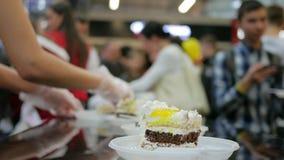 Nahaufnahme des Sahnekuchens im Einweggeschirr auf Tabelle, Stück der Torte auf Platte in den Händen, verwischte Schattenbilder,  stock footage