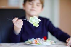 Nahaufnahme des Salats auf der Gabel, die durch den glücklichen Kinderjungen isst frischen Salat mit unterschiedlichem Gemüse als lizenzfreies stockfoto