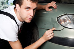 Nahaufnahme des schädigenden Autos geprüft vom Mechaniker stockbild