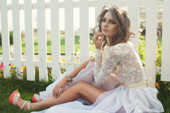 Nahaufnahme des schönen Mädchens mit dunklem Make-up im langen weißen Kleid Stockfotografie