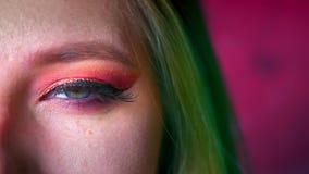 Nahaufnahme des schönen weiblichen Augenmakes-up mit rosa Schatten und Gold-eyeline Grünes Haar auf dem feenhaften rosa Hintergru stock video footage
