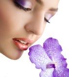 Nahaufnahme des schönen zarten weiblichen Gesichtes mit violetter Orchidee Lizenzfreie Stockfotografie