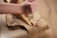 Nahaufnahme des Schnitts des italienischen Parmesankäseparmesankäses auf hölzernem Schneidebrett Lizenzfreie Stockbilder