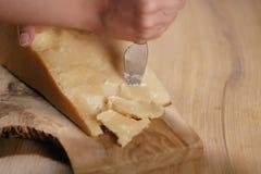 Nahaufnahme des Schnitts des italienischen Parmesankäseparmesankäses auf hölzernem Schneidebrett Stockfoto