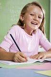 Nahaufnahme des Schulemädchenschreibens im Notizbuch Stockbild