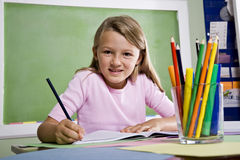 Nahaufnahme des Schulemädchenschreibens im Notizbuch Stockfotos