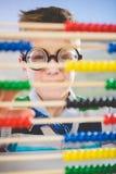 Nahaufnahme des Schulkindes schauend durch Abakus im Klassenzimmer Stockbilder