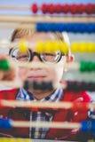 Nahaufnahme des Schulkindes schauend durch Abakus im Klassenzimmer Lizenzfreie Stockfotos